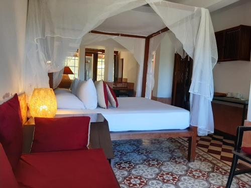 A bed or beds in a room at Villa Louise Hue Beach Boutique Hotel