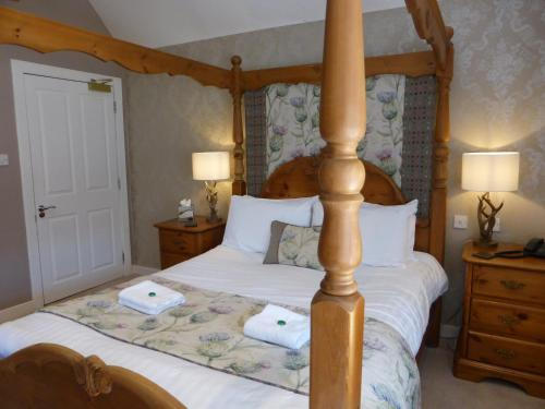 A bed or beds in a room at Glen Clova Hotel & Luxury Lodges