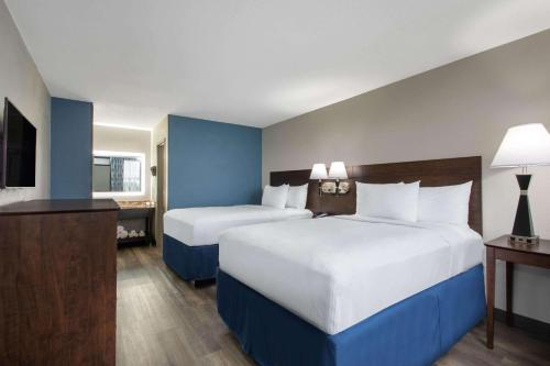 A bed or beds in a room at Days Inn by Wyndham Orlando Conv. Center/International Dr