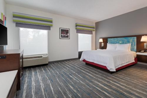 A bed or beds in a room at Hampton Inn & Suites Orlando International Drive North