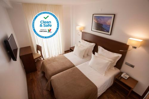 A bed or beds in a room at Hotel Miramar - São Pedro de Moel