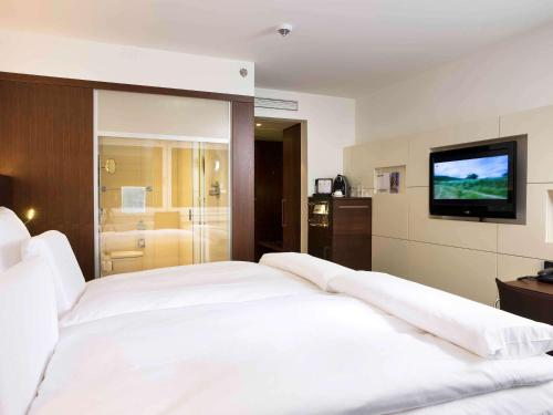 A bed or beds in a room at Pullman Cologne