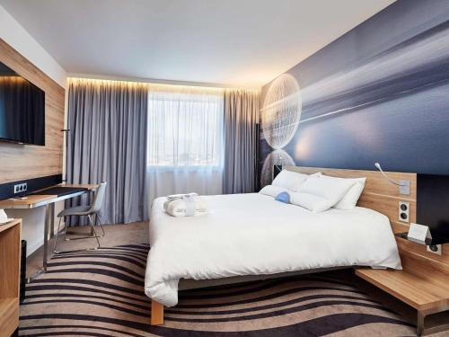 A bed or beds in a room at Novotel Kraków Centrum