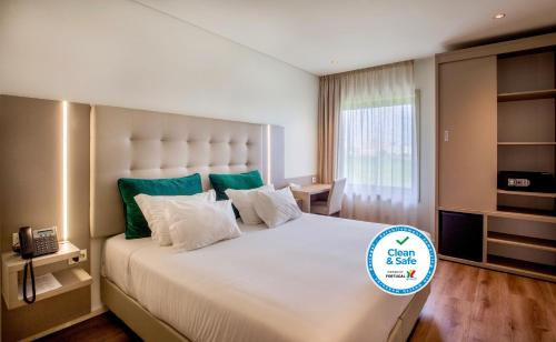 A bed or beds in a room at Oporto Airport & Business Hotel