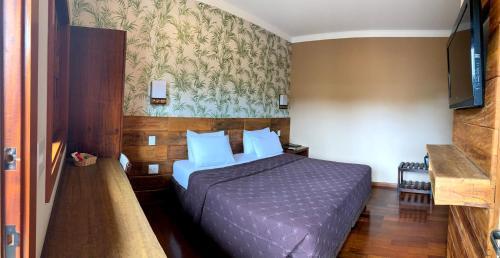A bed or beds in a room at Hotel Pousada Santa Rita