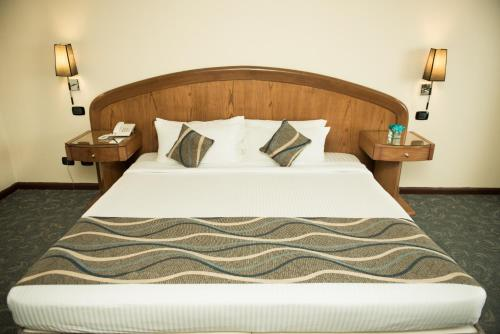 A bed or beds in a room at Cherry Maryski Hotel
