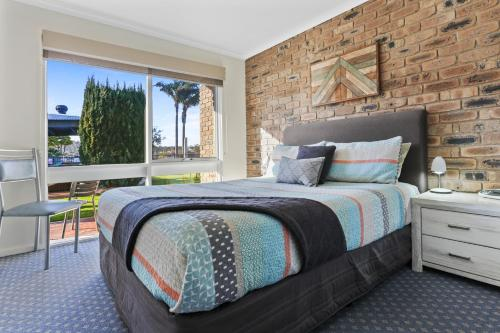 A bed or beds in a room at Lakeside Holiday Apartments Merimbula