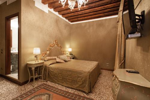 A bed or beds in a room at Hotel Al Ponte Mocenigo