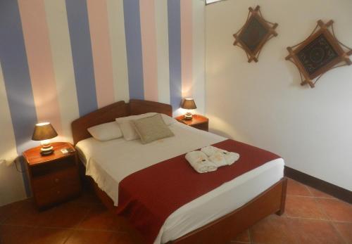A bed or beds in a room at El Cauchero Hotel