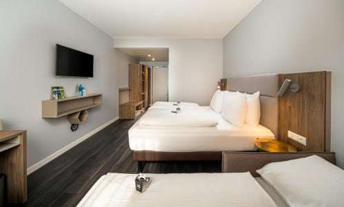 A bed or beds in a room at Arthotel ANA Soul Oberhausen