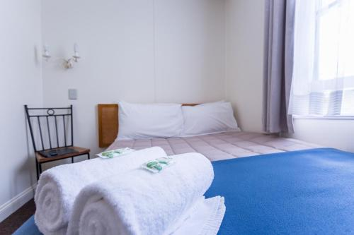 A bed or beds in a room at The Greytown Hotel
