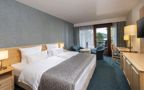 A bed or beds in a room at Maritim Titisee Hotel