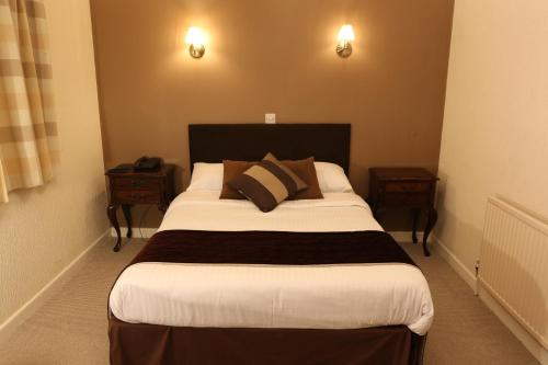 A bed or beds in a room at The Cedars Hotel, Loughborough
