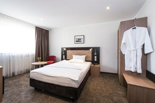 A bed or beds in a room at Astor und Aparthotel