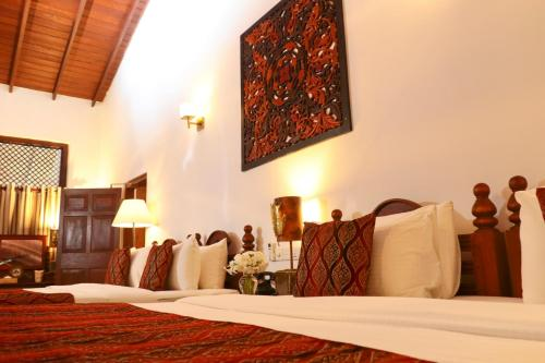 A bed or beds in a room at The Heritage Hotel Galle Fort