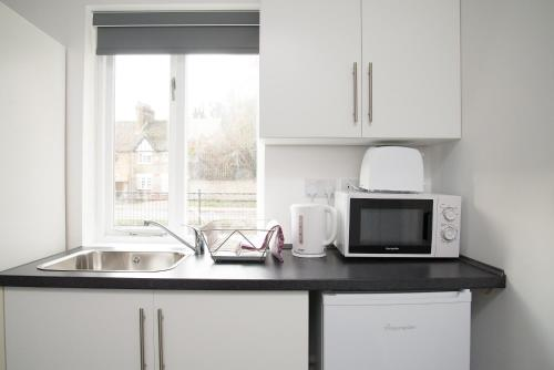 A kitchen or kitchenette at TLK Apartments and Hotel - Orpington