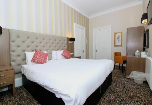 A bed or beds in a room at Ambassador Hotel
