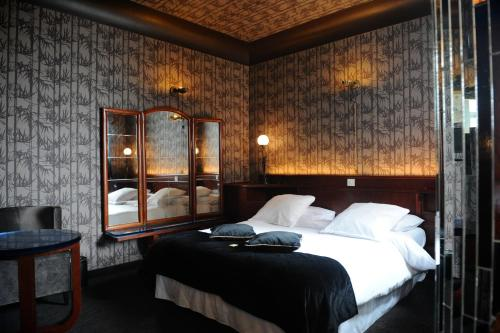 A bed or beds in a room at Le Berger Hotel