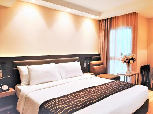A bed or beds in a room at Amora NeoLuxe Suites Hotel