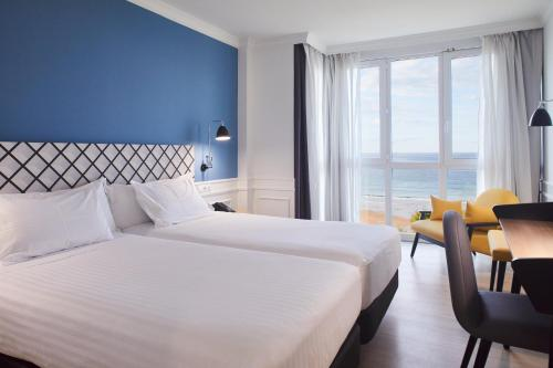 A bed or beds in a room at Silken Río Santander