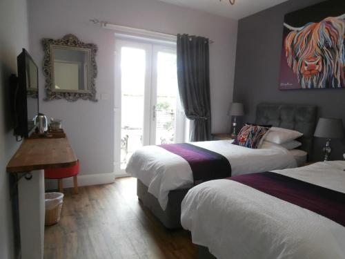 A bed or beds in a room at Angel Cottage