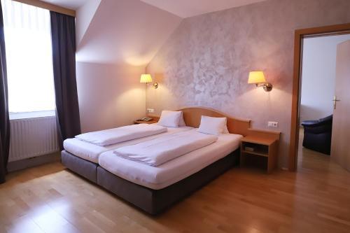 Ein Bett oder Betten in einem Zimmer der Unterkunft Stadthotel Pinkafeld
