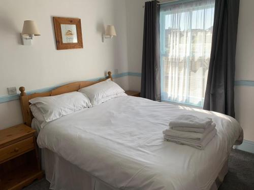 A bed or beds in a room at St Tudwals Inn