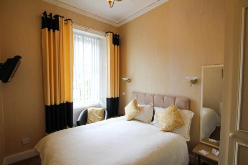 A bed or beds in a room at Dunallan Guest House