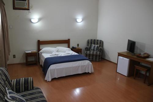 A bed or beds in a room at Hotel São Lucas