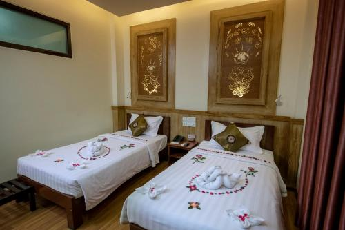 A bed or beds in a room at UCT Taunggyi Hotel