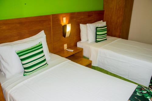 A bed or beds in a room at Quality Suites Natal Ponta Negra