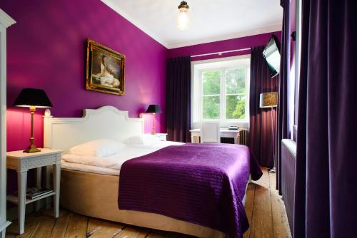 A bed or beds in a room at Hotel Hellstens Malmgård