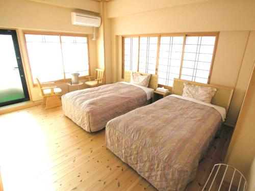 A bed or beds in a room at Minshuku Inn Shirahama Ekinoyado