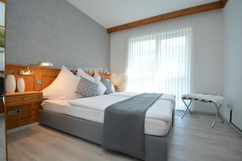 A bed or beds in a room at Hotel Haus Gimken