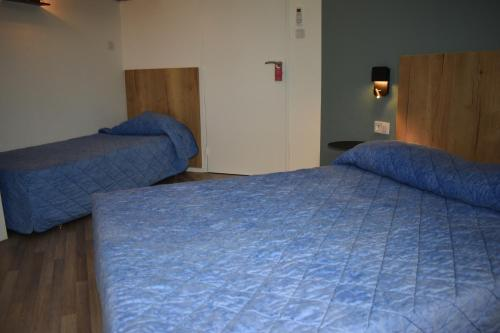 A bed or beds in a room at Cat'Hotel