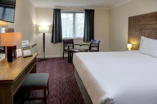 A bed or beds in a room at Best Western Buckingham Hotel