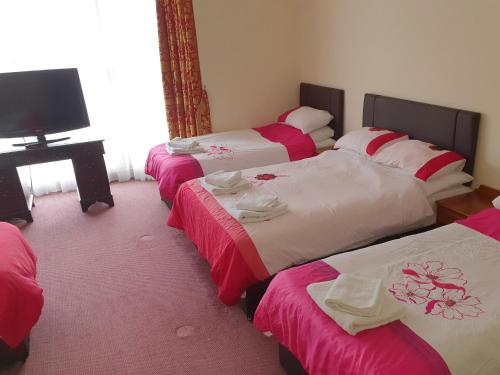 A bed or beds in a room at The Windmill Family & Commercial Hotel
