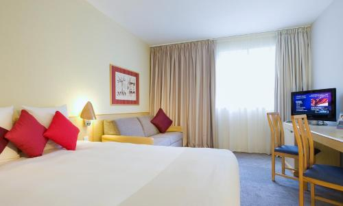 A bed or beds in a room at Novotel Manchester West