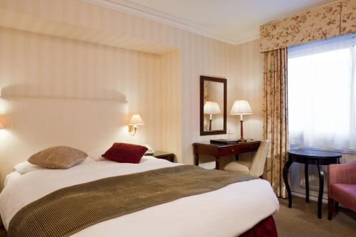 A bed or beds in a room at Mercure Banbury Whately Hall Hotel