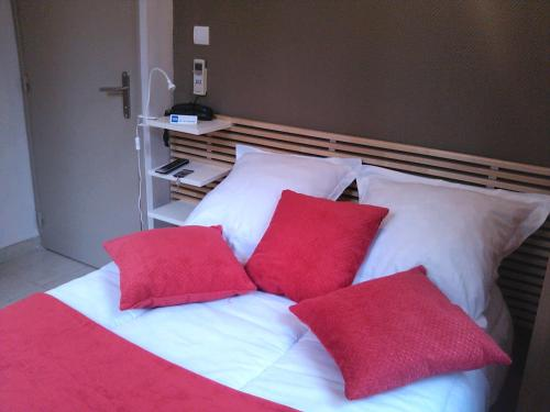 A bed or beds in a room at Hôtel de l'Ariana