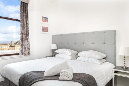 A bed or beds in a room at Kelpies Serviced Apartments