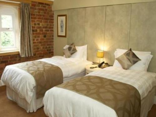 A bed or beds in a room at Carriages Telford