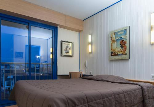 A bed or beds in a room at Hotel Arcantis Le Voltaire