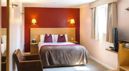 A bed or beds in a room at OYO Luton Hotel