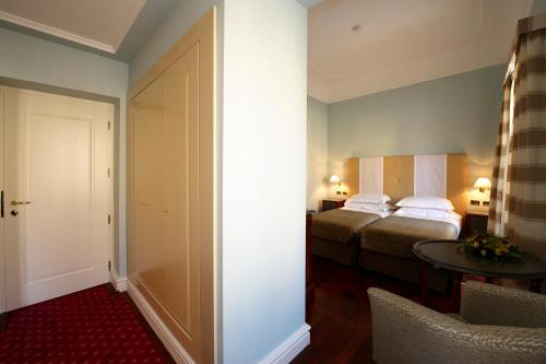 A bed or beds in a room at Grand Hotel Piazza Borsa