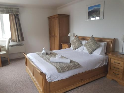 A bed or beds in a room at Loch Long Hotel