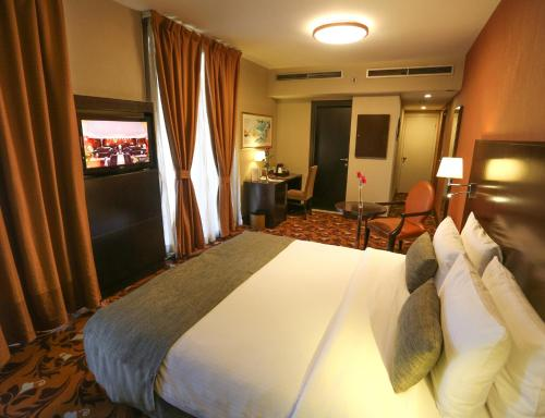 A bed or beds in a room at Babylon Rotana Hotel