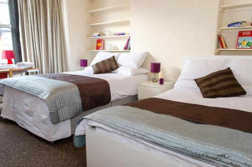 A bed or beds in a room at Campbells Guest House