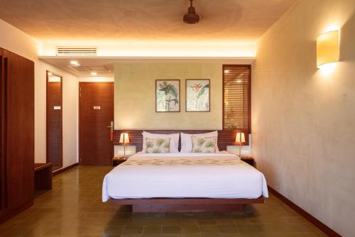 A bed or beds in a room at Penh House Hotel
