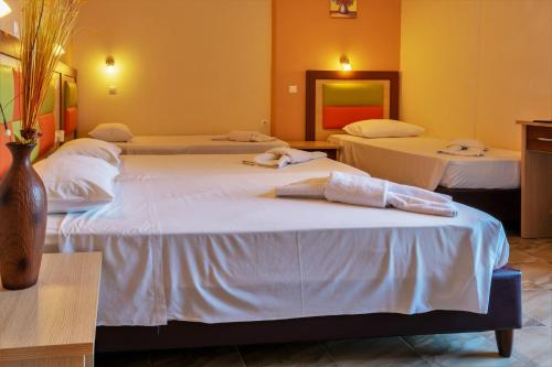 A bed or beds in a room at Maltezos Hotel